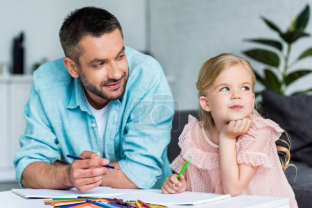 father and cute little daughter drawing with colored pencils together at home