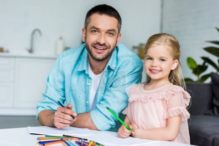 happy father and daughter drawing with colored pencils and smiling at camera