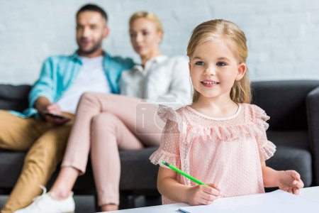 adorable smiling child holding pencil while parents sitting behind at home