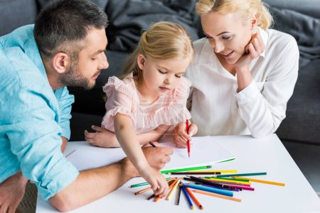 high angle view of family with one child drawing with colored pencils together at home