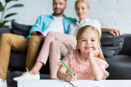 adorable child drawing with pencil and smiling at camera while parents sitting behind