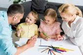 vue d'angle élevé des heureux parents avec enfants petits mignons, réunissant à la maison