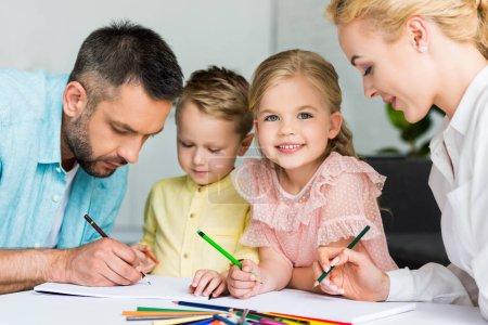 Foto de Felices padres con niños lindos dibujo juntos en casa - Imagen libre de derechos