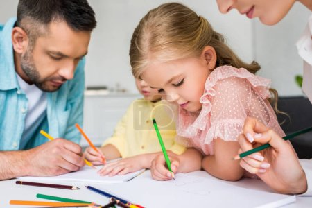cropped shot of parents with cute little children drawing with colored pencils at home