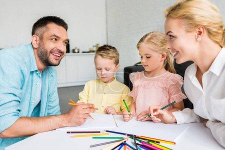 Photo pour Parents heureux avec deux petits enfants dessin avec des crayons de couleur à la maison - image libre de droit