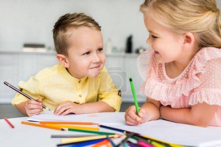 Foto de Adorables niños sonriendo unos a otros mientras dibujo con lápices de colores juntos - Imagen libre de derechos