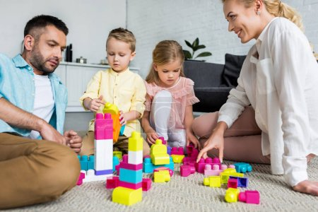 parents with adorable little kids sitting on carpet and playing with colorful blocks