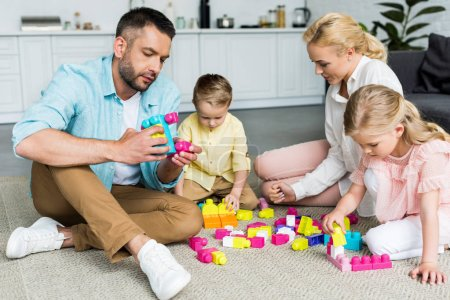 family with two little children sitting on carpet and playing with colorful blocks