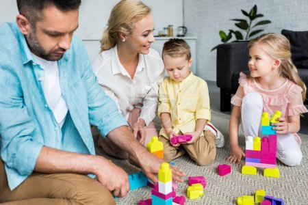 happy family with two kids playing with colorful blocks at home