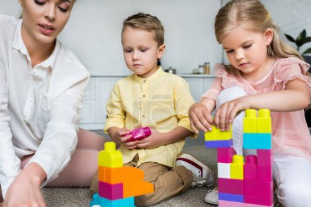 cropped shot of mother with cute little kids playing with colorful blocks at home