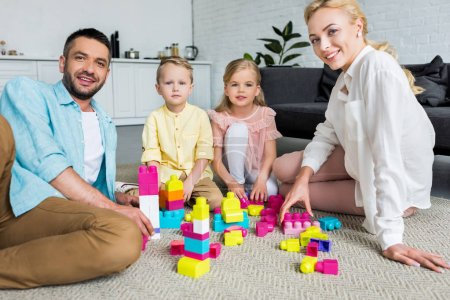 happy family smiling at camera while playing with colorful blocks at home