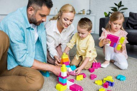 Photo pour Parents d'adorables petits enfants jouant avec des blocs colorés à la maison - image libre de droit