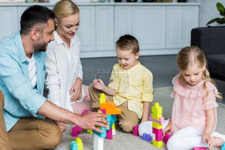 happy parents with cute little kids playing with colorful blocks at home