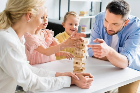 Photo for Happy family with two kids playing with wooden blocks at home - Royalty Free Image