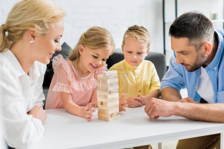 happy family with two children playing with wooden blocks at home