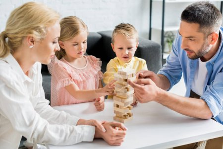 family with two children building tower from wooden blocks at home