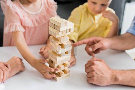plan recadré de la famille avec deux enfants construisant tour de blocs de bois à la maison