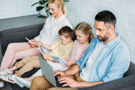 family with two kids sitting on sofa and using digital devices at home