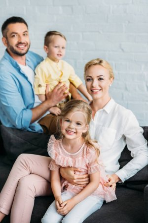 happy family with two adorable kids smiling at camera at home