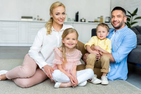 Photo for Happy family with two kids smiling at camera while sitting together at home - Royalty Free Image