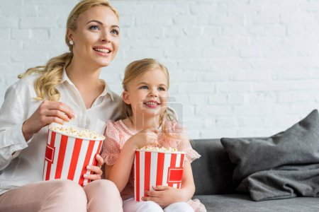 happy mother and daughter eating popcorn and looking away at home