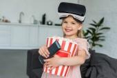 adorable enfant souriant dans le casque de réalité virtuelle maintenant boîte avec pop corn et télécommande