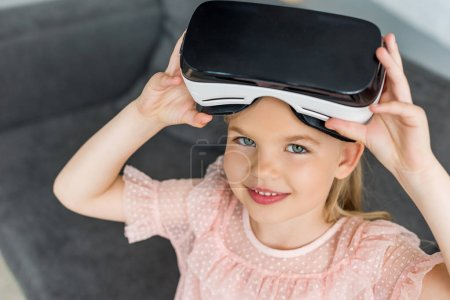 high angle view of adorable child in virtual reality headset smiling at camera at home
