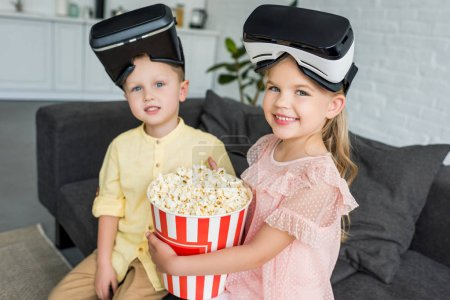 Photo for Adorable kids in virtual reality headsets holding popcorn box and smiling at camera - Royalty Free Image