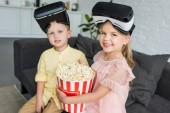 adorable kids in virtual reality headsets holding popcorn box and smiling at camera