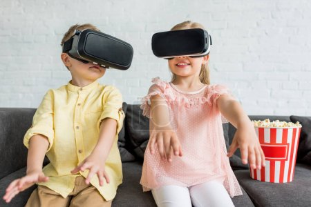 adorable little children using virtual reality headsets while sitting on sofa at home