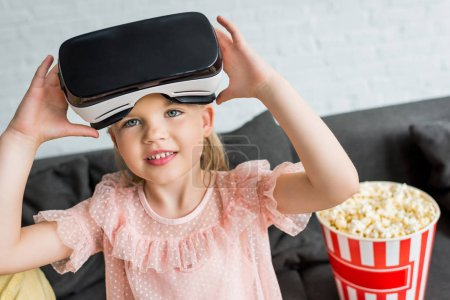 adorable child in virtual reality headset smiling at camera at home