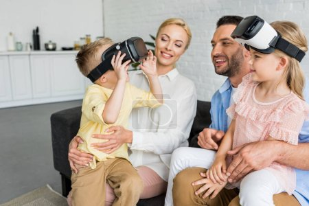 happy parents looking at cute little kids using virtual reality headsets at home
