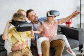 happy family with two kids using virtual reality headsets at home