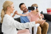 happy parents looking at cute little daughter using virtual reality headset at home