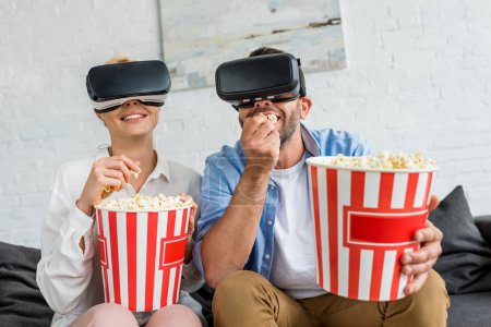 Photo for Happy couple in virtual reality headsets eating popcorn together at home - Royalty Free Image