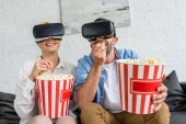 happy couple in virtual reality headsets eating popcorn together at home