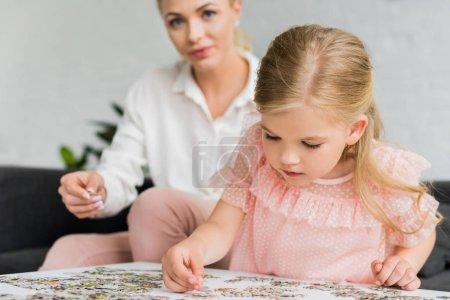 adorable little child playing with puzzle pieces while mother sitting behind