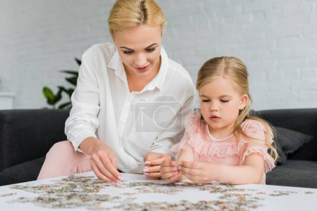 beautiful mother and daughter playing with jigsaw puzzle at home