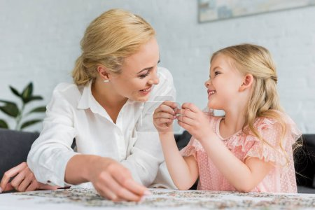 happy mother and daughter smiling each other while playing with puzzle pieces at home