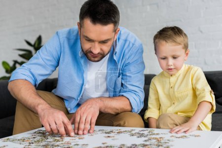 father and cute little son playing with jigsaw puzzle together at home