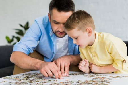 focused father and son playing with jigsaw puzzle together at home