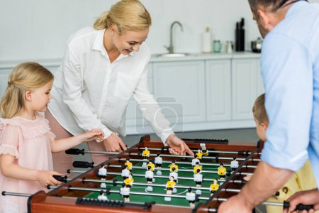 happy family with two kids playing table football together at home