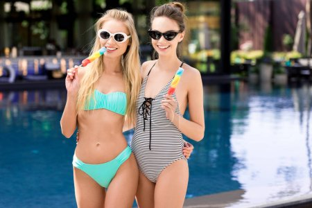 happy young embracing women in swimsuit and bikini with popsicles looking at camera at poolside