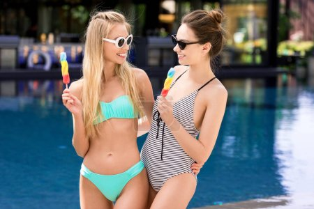 happy young embracing women in swimsuit and bikini with popsicles at poolside