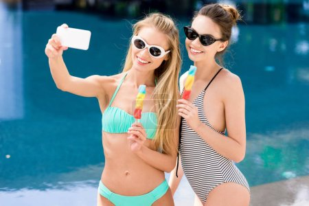 happy young women in swimsuit and bikini taking selfie with popsicles at poolside