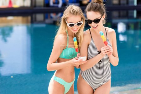 beautiful young women in swimsuit and bikini with popsicles at poolside