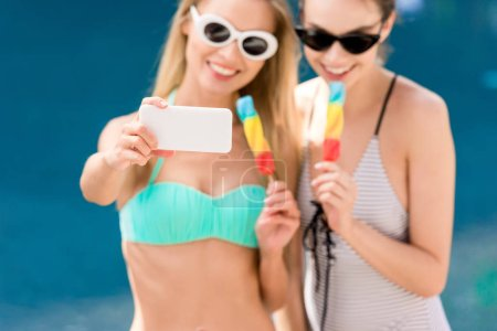 attractive young women in swimsuit and bikini taking selfie with popsicles at poolside
