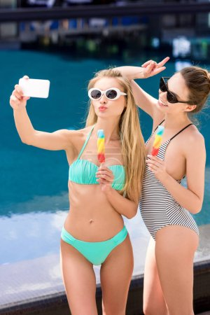 beautiful young women in swimsuit and bikini taking selfie with popsicles at poolside