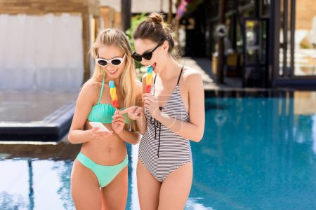 happy young women in swimsuit and bikini eating popsicles and using smartphone at poolside