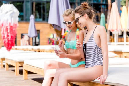 beautiful young women in swimsuit and bikini with popsicles using smartphone while sitting on sun lounger at poolside